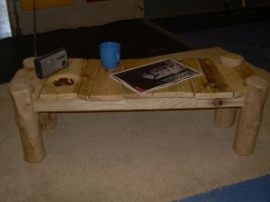 Low slung coffee table.  Pallet wood top, driftwood legs, pallet wood rails.